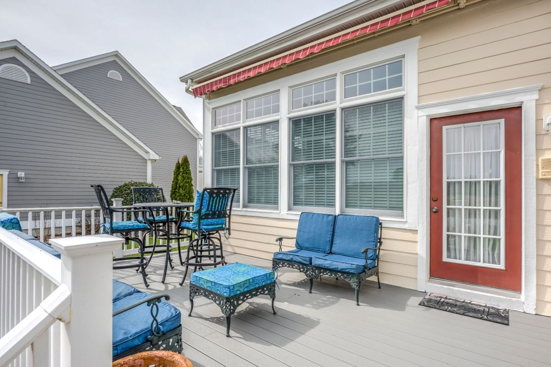 October Glory Exterior in Ocean View DE - Lower Deck with White Railing and Red Awning Cover