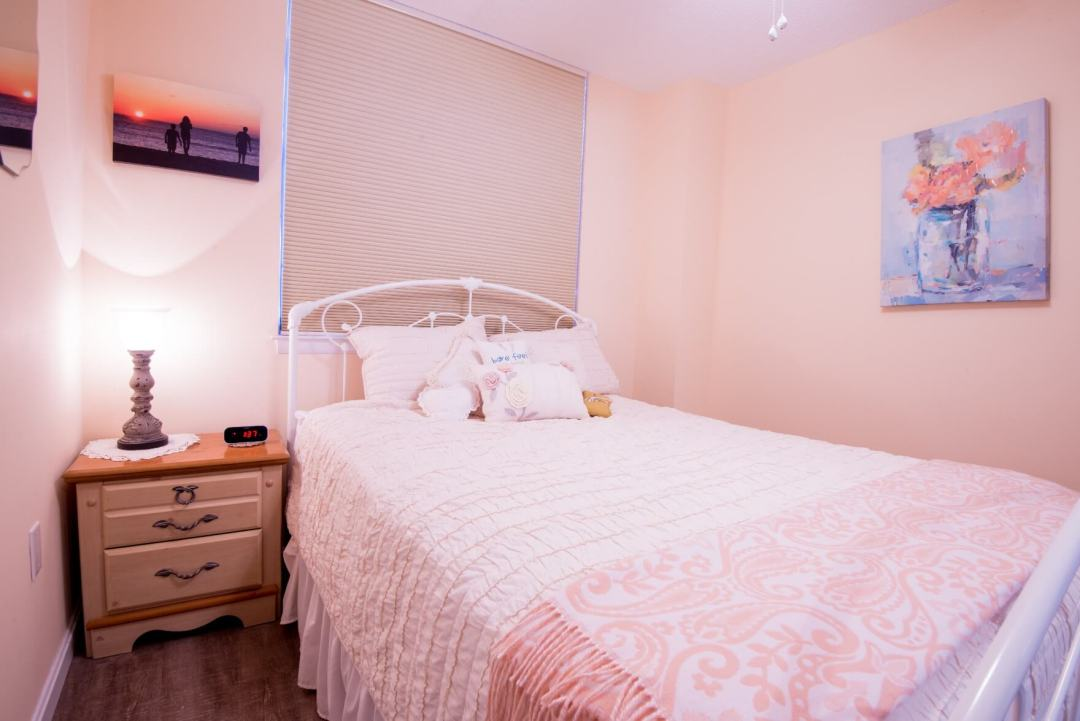 Sea Colony Condo Renovation Bethany Beach, DE Peach Color Bedroom with Dark Wood Floor and Light Wood Night Stand