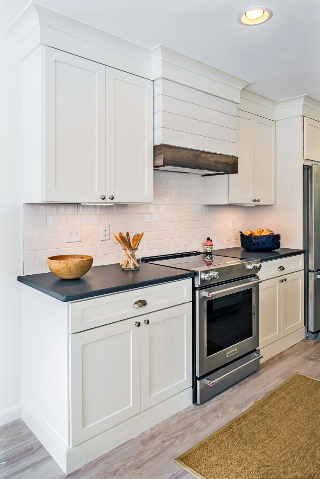 Kitchen in Wellington Parkway, Bethany Beach DE with White Cabinets, Black Granite Countertop and White Tile Backsplash
