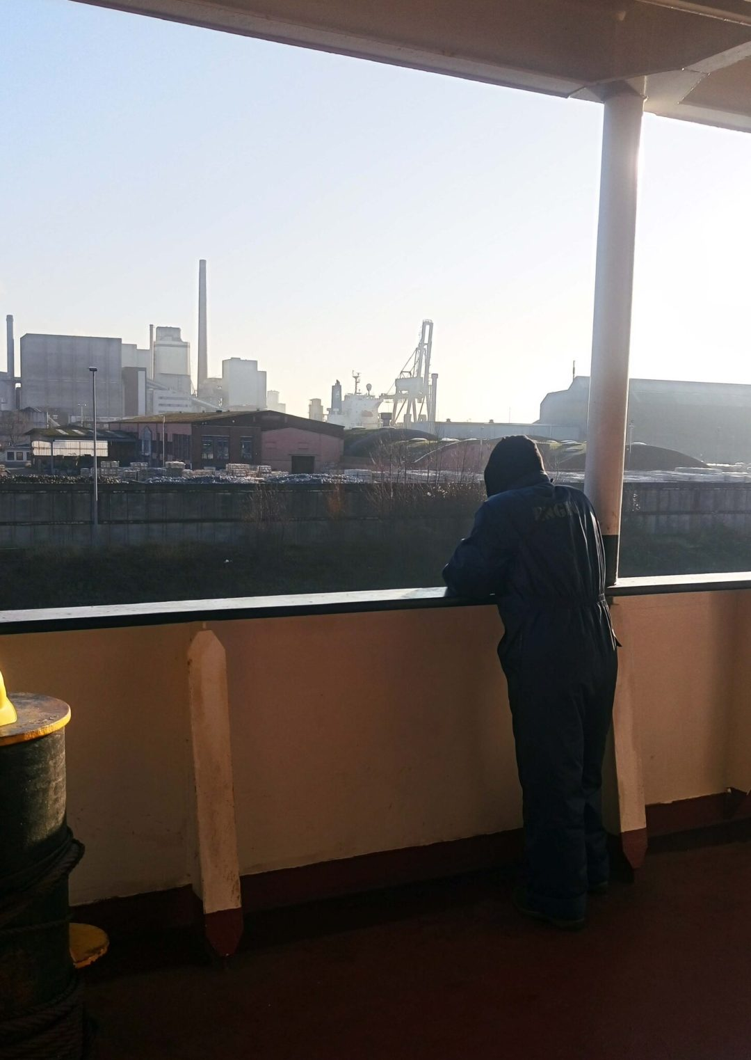 Seafarer in the ship's side watching the waters.