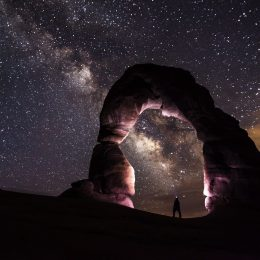 person standing under a rock formation on a starry night
