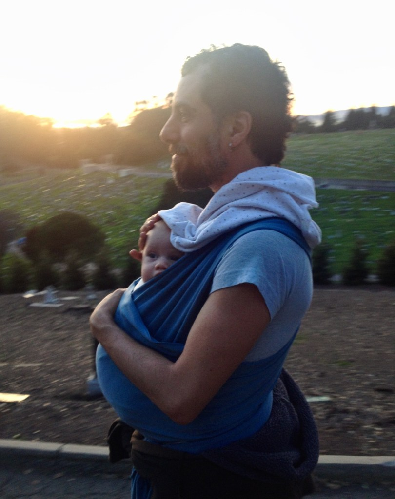 Sean outside with sunset, carrying an infant in a blue sling