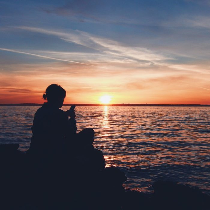 Image Of Person Sitting Out By The Water At Sunset - Search Influence