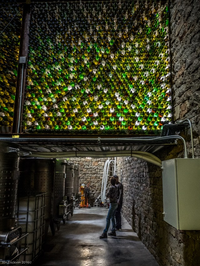 View of the vats in the cave and how the old wine bottle glass lets in some natural light.