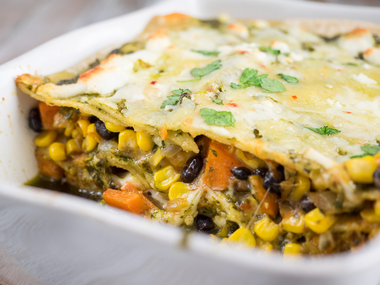 Sweet Potato Enchilada Casserole | An easy enchilada casserole that is hearty and ready to feed a crowd. Filled with sweet potatoes, black beans, and corn, topped with a homemade chimichurri sauce. | SeasonedVegetable.com