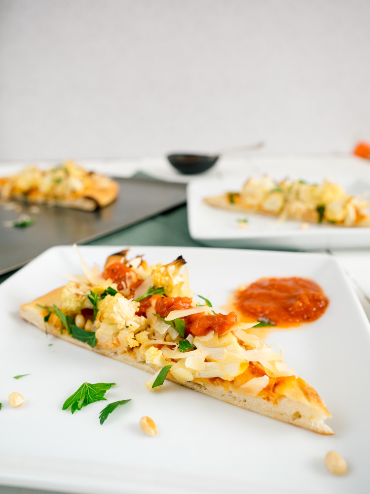 Roasted Cauliflower Flatbread Pizza | Roasted cauliflower flatbread pizza is an easy lunch or dinner ready in 30 minutes. Crunchy cauliflower is paired with tomato sauce, parmesan cheese, pine nuts, lemon and parsley on fluffy flatbread. | SeasonedVegetable.com #pizza #vegetarian #flatbread