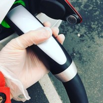 Image of Tesla Supercharger plug beingheld by a person wearing surgical gloves