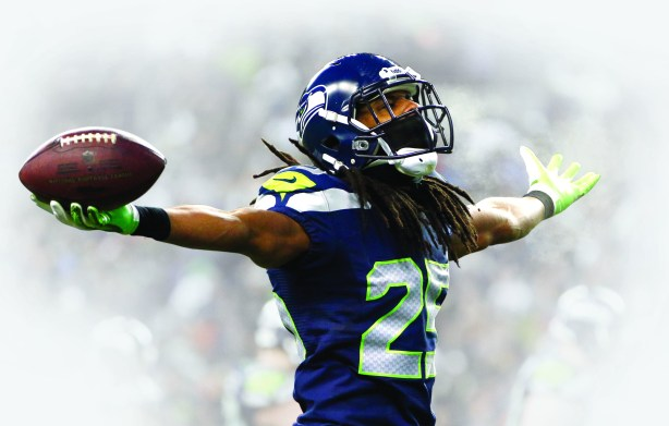 Richard Sherman salutes the 12th-Man after intercepting a pass. Photo: The Seattle Times