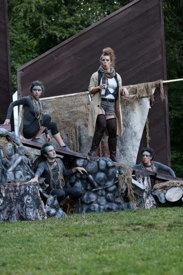 """Donna Wood as Trinculo (center) surrounded by the Ariels (l-r) Olivia Hartshorn, Scott Ward Abernethy, and Tonya Andrews in Seattle Shakespeare Company's 2013 Wooden O production of """"The Tempest."""""""