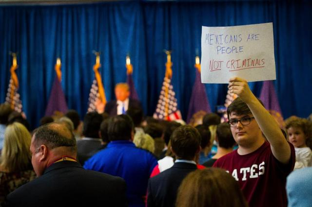 Young man presenting an alternate viewpoint at a Trump political rally in Manchester, NH. Courtesy of the Concord Monitor.