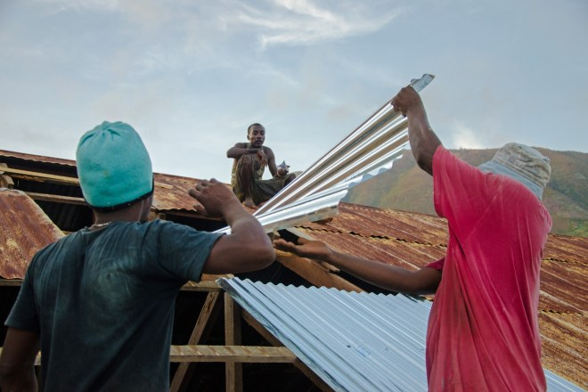 Men repair the roof of a home in Haiti following Hurricane Matthew, which left hundreds dead and many more homeless. Photo credit: © Georges Harry Rouzier/Kolektif 2D