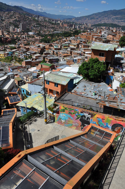 Comuna 13 tour. Comuna 13 remains one of Medellín's poorest and most violent neighborhoods. It is not recommended to visit without a guide. Medellín recently installed a giant outdoor escalator to help integrate its residents with the rest of the city. Previously they had to climb stairs the equivalent of a 30-story building to get to and from the city center.