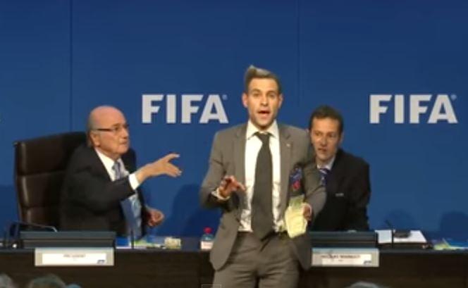 Il burlone Simon Brodkin contesta Blatter con una mazzetta di banconote