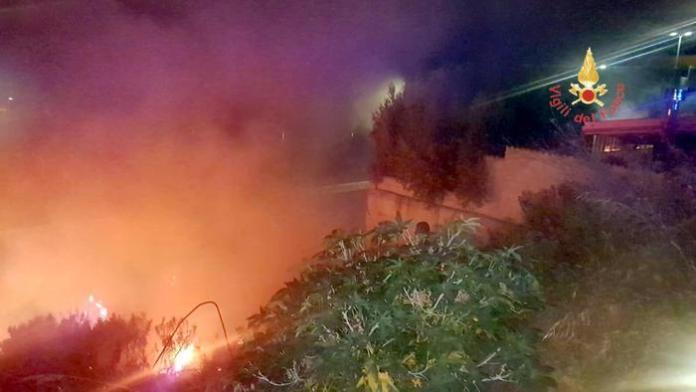 Vigili del fuoco impegnati a spegnere un incendio di sterpaglie