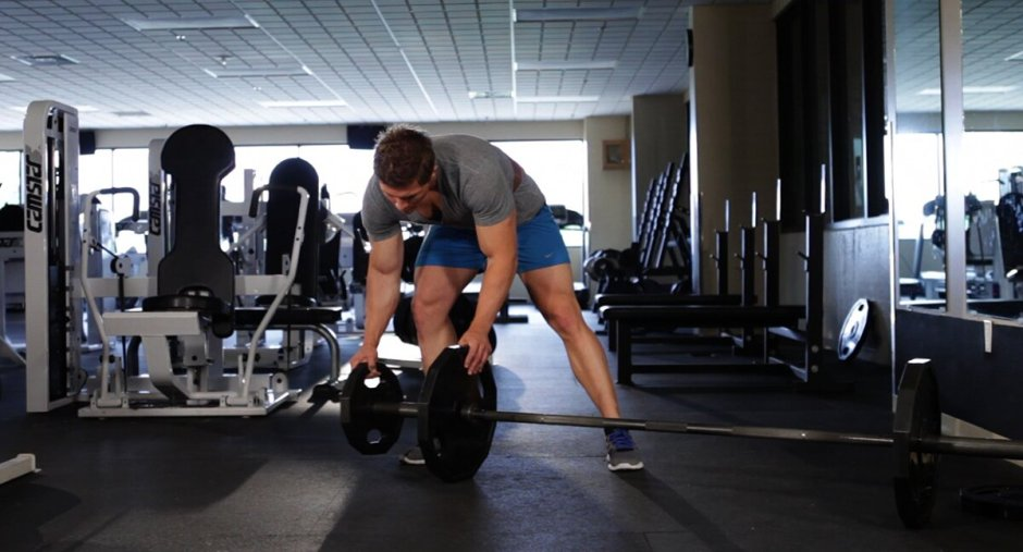 Loading weight plates on a barbell.