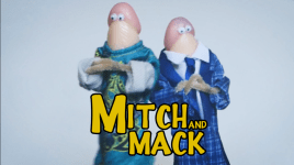 Two flesh colored dildos with googly-eyes. One dressed in a long shirt, the other in shirt with tie and smoking jacket with text: Mitch and Mack