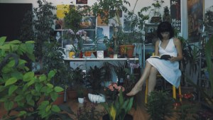 Woman in a white dress with a book sounded by house plants.