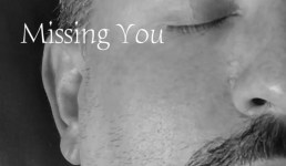black and white close up of right side of man's face, text reads Missing You.