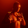 Still image from the short film, Progressive Touch of a dancing naked woman with her hair slicked back.