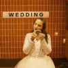 Still from the short film, Sologamy, of a woman in a wedding dress applying make-up to her face while waiting for a train. Wedding is spelled out on the metro station tiles behind her.g