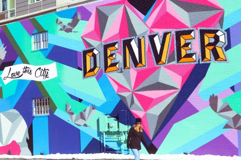 A girl walking in front of street art in Denver, Colorado