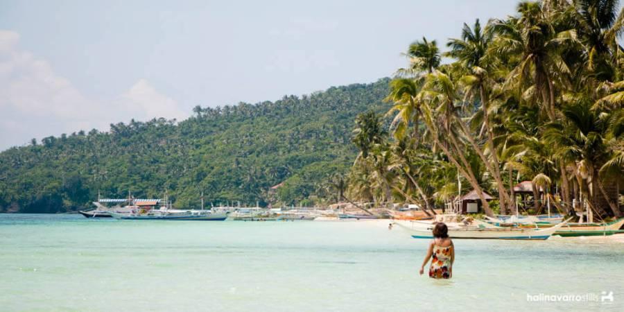 girl walking into the water at carabao island beach