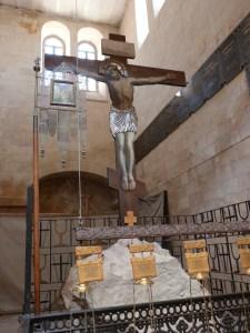 Crucifix standing over piece of rock of Calvary (Seetheholyland.net)