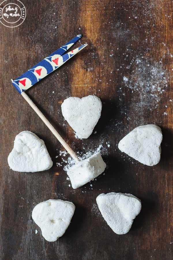 6 heart shaped vegan marshmallows on a wooden board.
