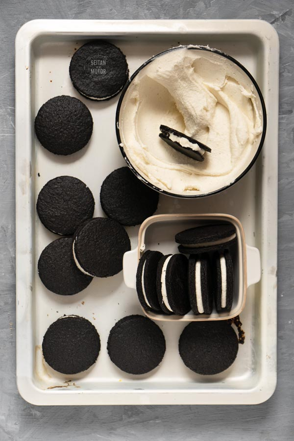 A batch of oreo cookies and a bowl of frosting on a baking tray.