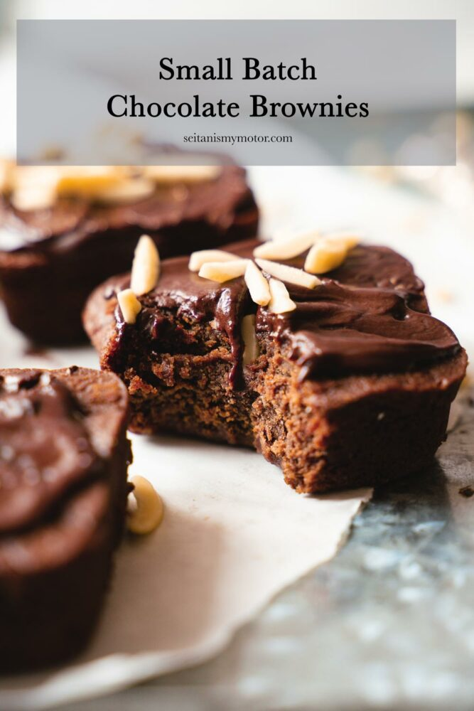 This picture shows three small batch chocolate brownies on a a piece of white parchment paper.