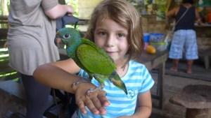 Quinn holding a green parrot