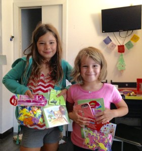 Mackenzie and Quinn stand with gifts of art supplies in front of the paper christmas tree we made