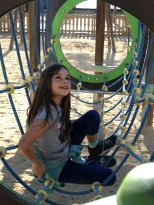 Mackenzie in a rope tube on a playground