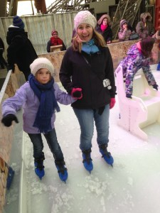 Amy holding Mackenzie's hand while she learns to ice skate at the Eiffel Tower