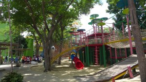 Three story playground with bridges and next connecting the rainbow colored structures