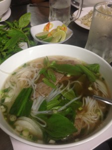 A bowl of noodle soup adorned with greens and bean sprouts