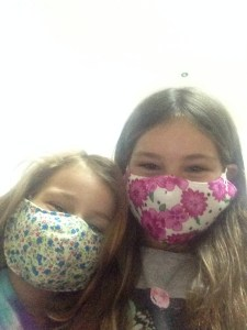 Mackenzie and Quinn pose with their pollution masks covering mouth and nose