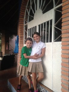 Picture of Mackenzie and Quinn in school uniforms of kaki skirts and white polo shirt (mack) and green t-shirt (Quinn) on first day of school