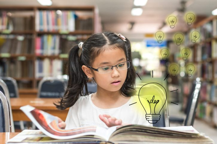 Innovative creative idea for copyrights law concept with kid surprised reading book with lightbulb in library