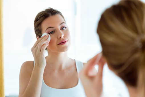 Canva - Beautiful Young Woman Is Cleaning Her Face While Looking in the
