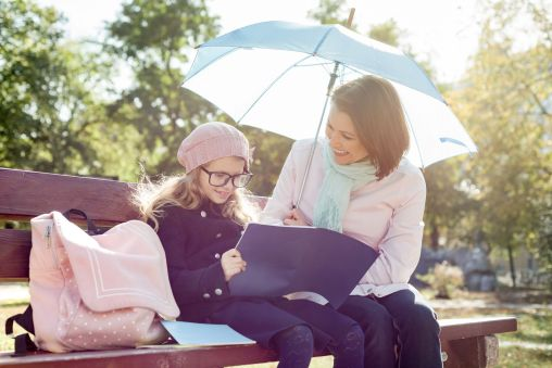 Canva - Mom and Daughter Talking, Laughing Sitting on Bench in the Park, Child with School Bag Reading Notebook