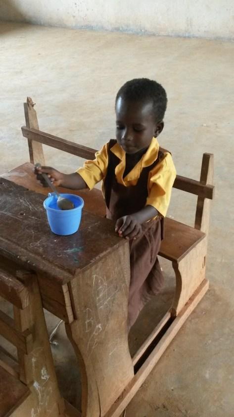 young girl sits at table eating porridge