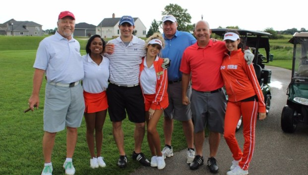 Hooters girls pose with a group of golfers
