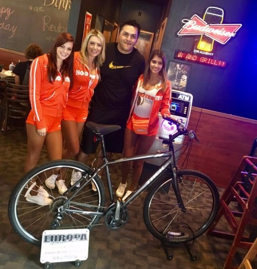 man poses with three women in front of newly won bicycle