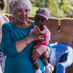 Mary Jane Oakland holds an infant in rural Ghana