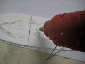 Artfully glop hot glue onto one side of the foam...