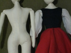 cloth dolls, one in costume, closeup from back