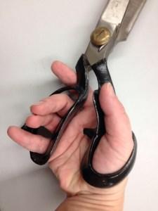 Hand on scissors