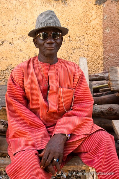A dressed up man enjoying the hot afternoon sitting on a wooden bench in Fadiout, Senegal. Photo by Marko Preslenkov.