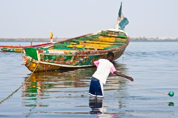 A kid setting up his fishnet in the shallow waters of the Senegal river in N'Dar Tout quarter of Saint-Louis, Senegal. Photo by Marko Preslenkov.